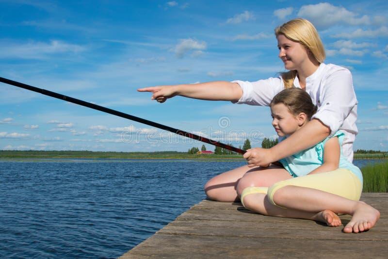 La mamma tiene la canna da pesca e la mano mostra sua figlia sull'attaccare, al pilastro, contro il contesto di bello paesaggio, immagini stock libere da diritti