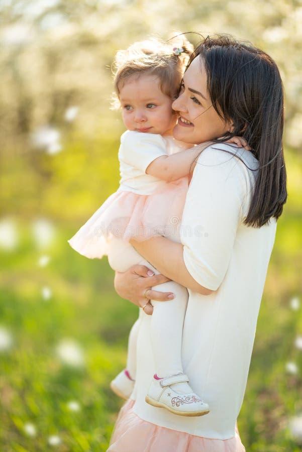La mamma tiene il bambino nelle sue armi in giardini di fioritura, festa della Mamma, l'8 marzo, l'umore della molla immagini stock libere da diritti
