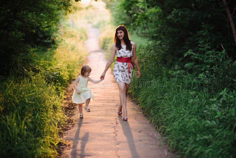 La mamma tiene la mano della figlia e cammina la passeggiata sulla natura alla luce del tramonto fotografia stock
