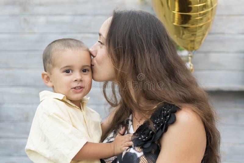 La mamma tiene un bambino lei armi e lo bacia delicatamente sulla guancia La mamma bacia delicatamente suo figlio immagini stock