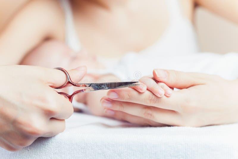 La mamma tonsured i chiodi sulle mani neonate facendo uso delle forbici del chiodo immagine stock
