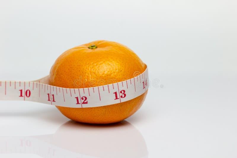 La mandarina fue envuelta por la cinta métrica fotos de archivo