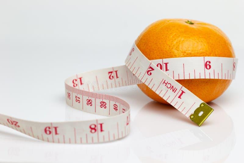 La mandarine a été enveloppée en mesurant la bande photos libres de droits