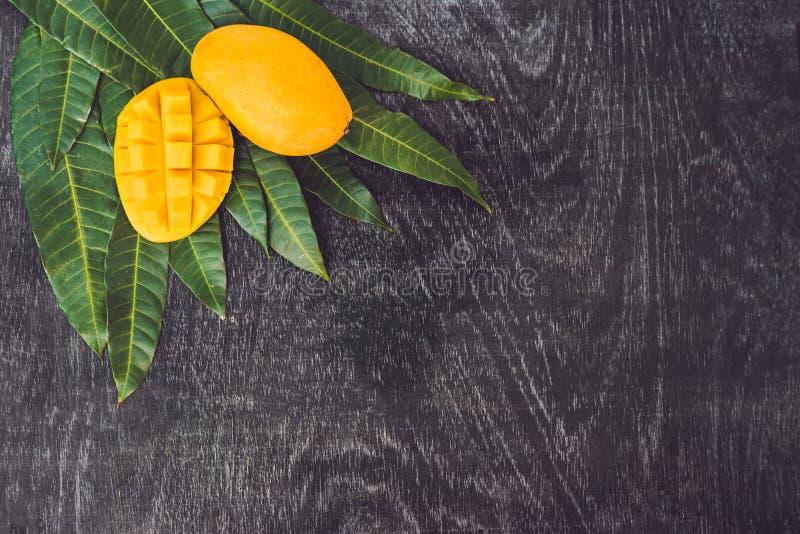 La mangue et la mangue part sur un vieux fond en bois image stock