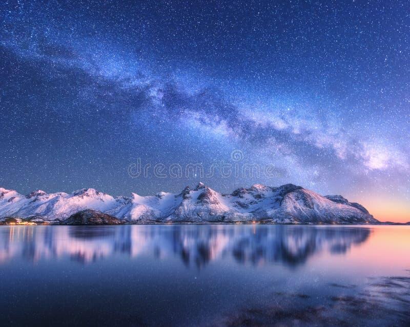 La manière laiteuse au-dessus de la neige a couvert les montagnes et la mer la nuit en hiver images libres de droits