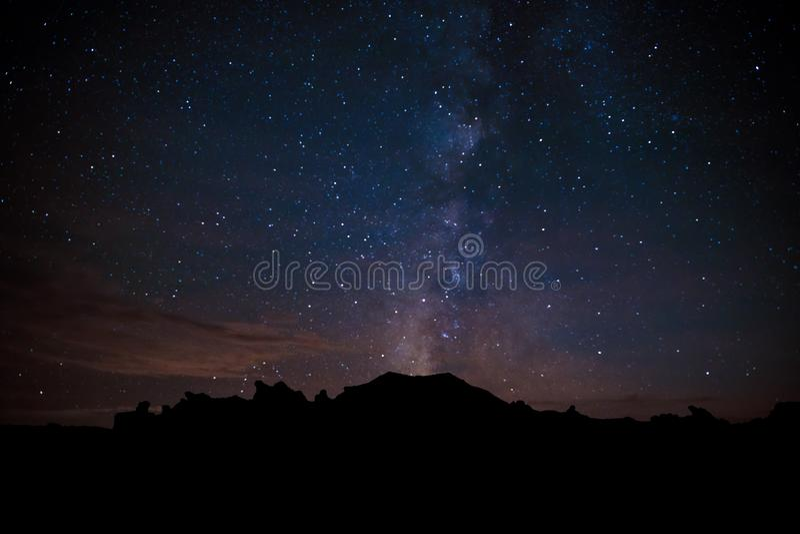 La manière laiteuse semble éclater d'une crête silhouettée contre un ciel étoilé dans les bad-lands de Bisti du Nouveau Mexique photo libre de droits