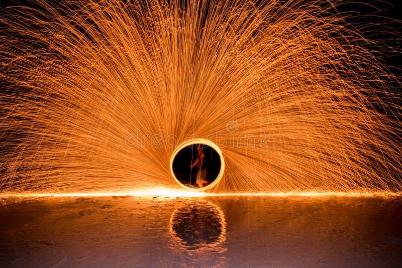 La manifestazione dacing del fuoco dell'oscillazione dell'uomo sulla spiaggia immagini stock libere da diritti