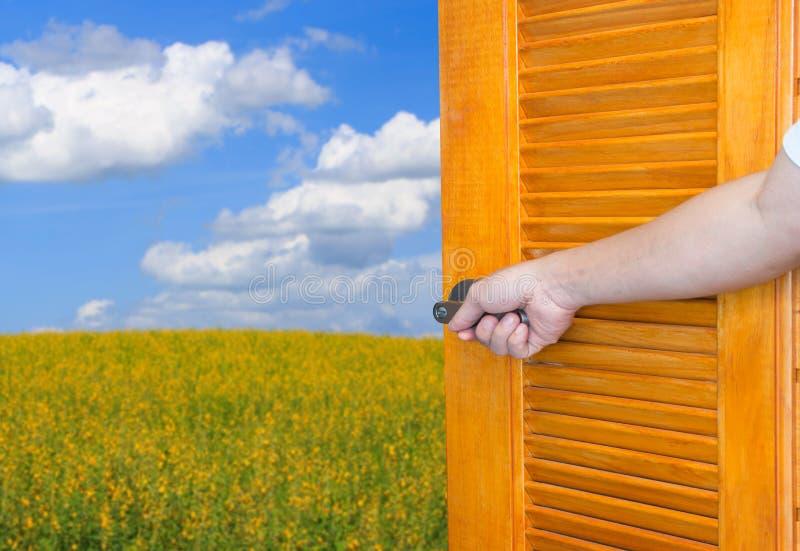 La maniglia della porta aperta della mano dell'uomo l'asse d'oscillazione o apre la porta vuota della stanza alla natura immagini stock libere da diritti