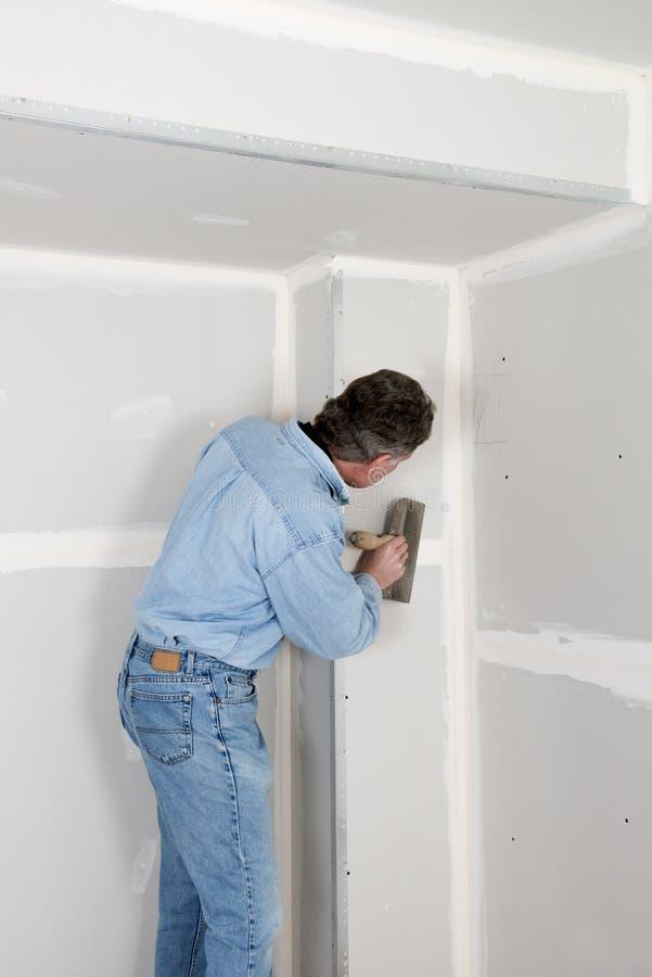 Las mejoras para el hogar, hombre del contratista instalan la mampostería seca imagenes de archivo