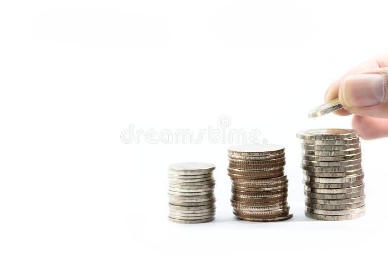 La mano è prende le monete dai capitali delle monete collocati correttamente in una fila immagine stock