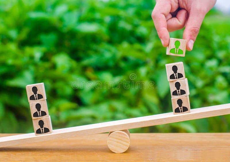 La mano añade un cubo con la imagen del empleado a la pila en las escalas El concepto de empleados de alquiler y de los appointme foto de archivo