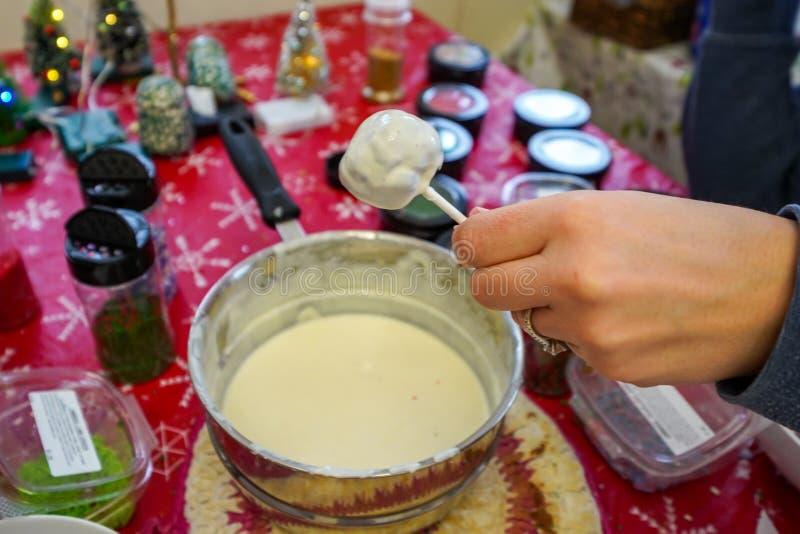 La mano adulta lleva a cabo un estallido de la torta sumergido en el chocolate blanco derretido, preparando la invitación dulce d imágenes de archivo libres de regalías