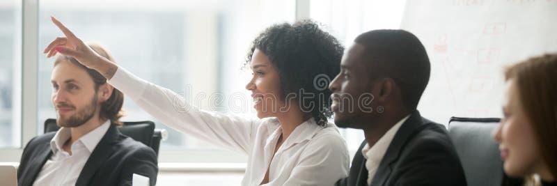 La mano africana dell'aumento della donna fa la domanda durante il seminario alla sala del consiglio fotografie stock libere da diritti