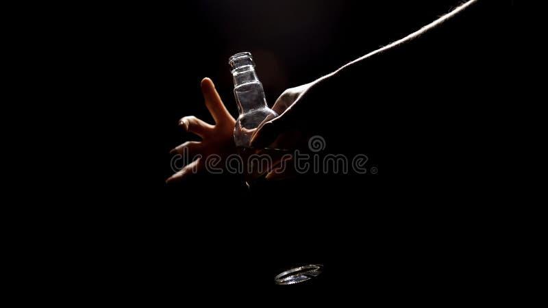 La mano alcohólica que toma la vodka de la oscuridad, desciende para basar, vida de la miseria fotos de archivo libres de regalías