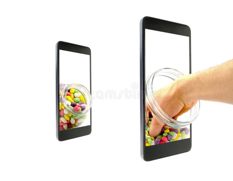 La mano allunga in un barattolo di vetro con la caramella variopinta nella glassa che va oltre lo schermo di uno smartphone isola fotografie stock