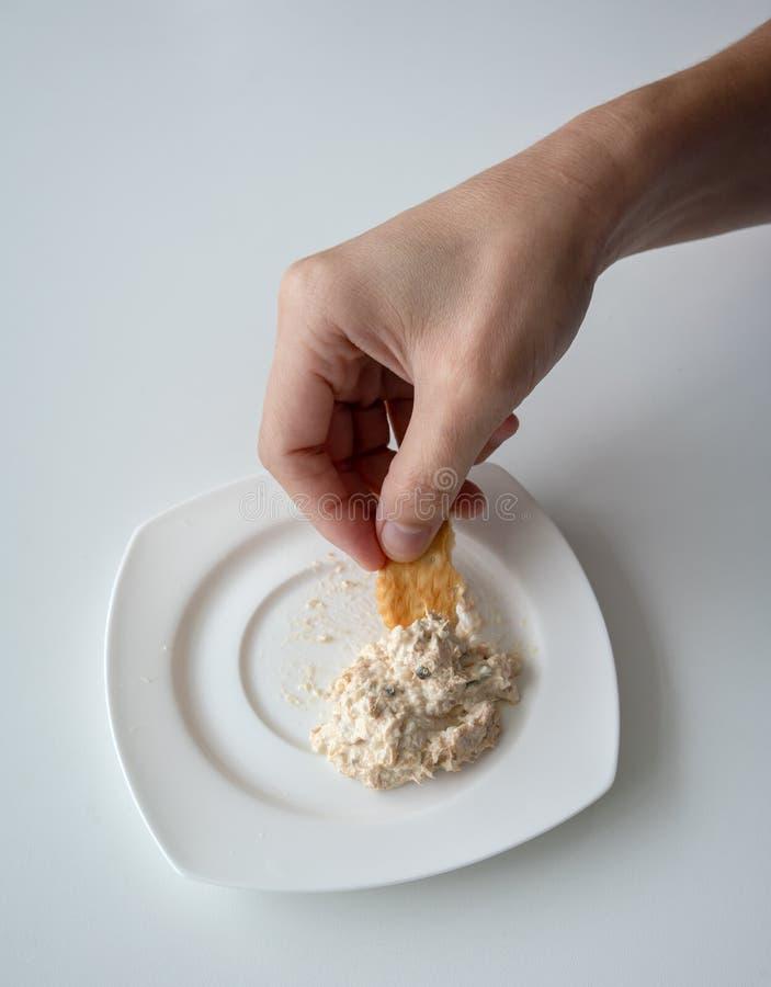 La mano alta chiusa che immerge il tonno si è sparsa in piatto bianco con mini crac fotografia stock libera da diritti