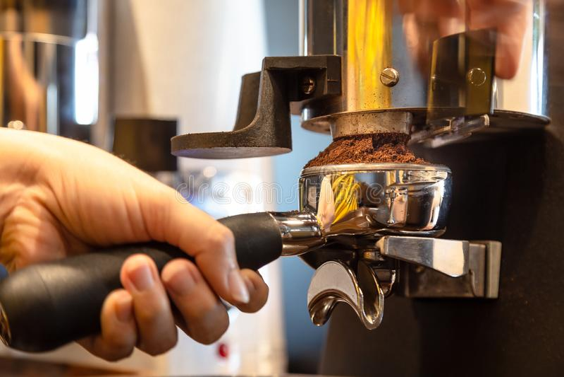 La mano alta vicina della donna che tiene il portafilter, barista della ragazza sta frantumando i chicchi di caffè arrostiti nell fotografie stock