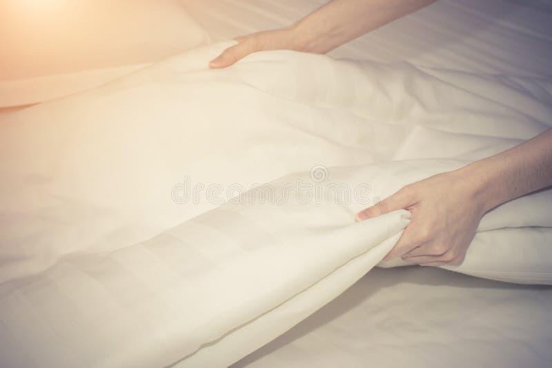 La mano alta vicina della donna ha installato il lenzuolo bianco nella camera di albergo fotografia stock
