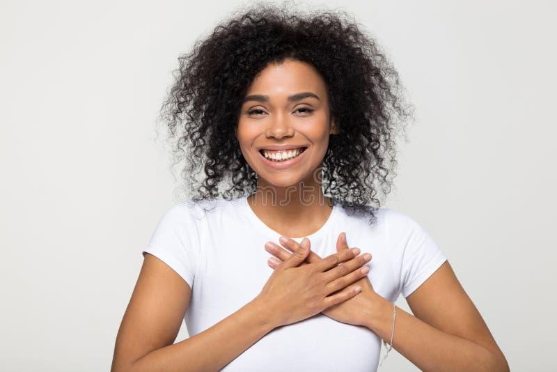 La mano americana de la tenencia de la mujer del retrato del Headshot en coraz?n siente gratitud fotos de archivo