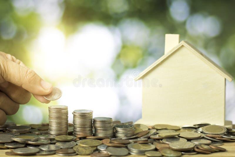 La mano apiló monedas del dinero con la casa modelo, concepto de las propiedades inmobiliarias imágenes de archivo libres de regalías