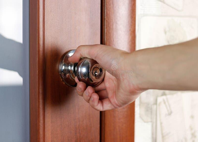 La mano apre la porta dalla maniglia Fine in su immagine stock