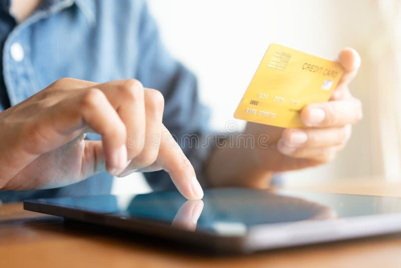 La mano ascendente cercana de hombres de negocios est? comprando en l?nea con una tarjeta de cr?dito E foto de archivo