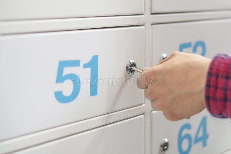 La mano ascendente cercana que lleva a cabo la llave abre la caja de banco d segura foto de archivo