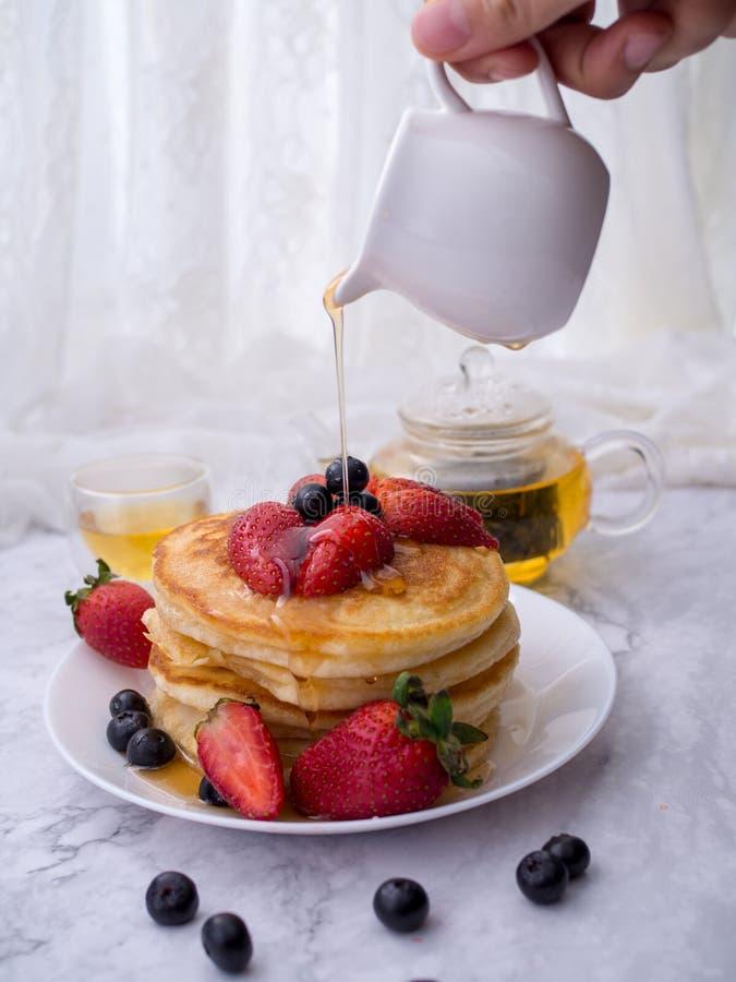 La mano ascendente cercana vierte la miel en las crepes, que están prendido superiores con las fresas de la frambuesa Pila de cre imagenes de archivo