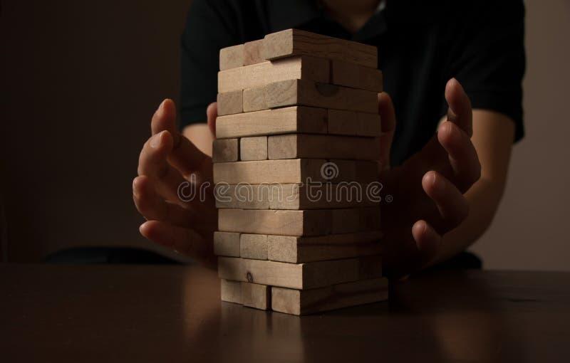 La mano asiatica della donna ha messo i blocchi di legno Rischio d'investimento ed incertezza nel mercato degli alloggi del bene  immagini stock