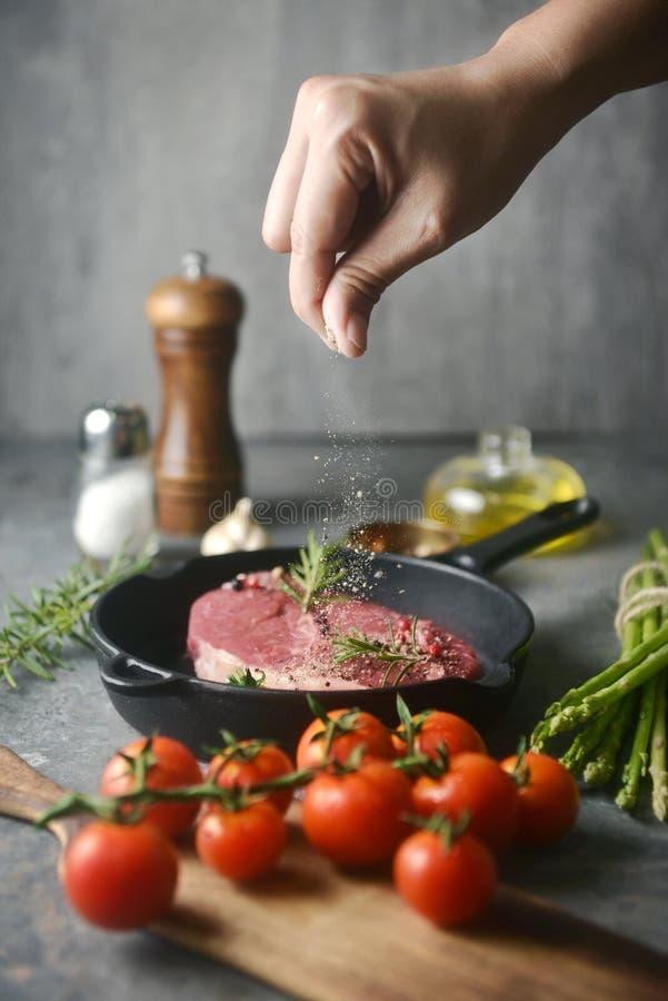 La mano asperja la pimienta para adoba la carne en cacerola del hierro en la parte inferior en fondo de los ingredientes tiros de fotografía de archivo libre de regalías