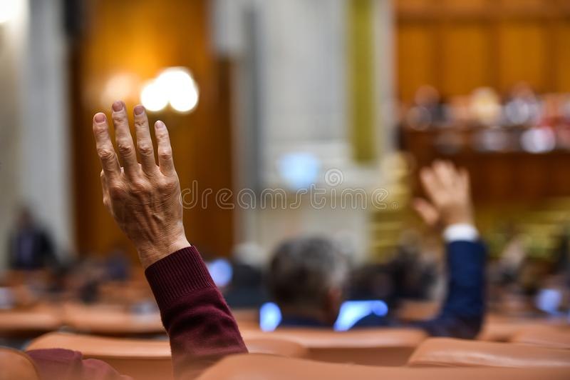 La mano aumentó en el aire durante un procedimiento de votación imagenes de archivo