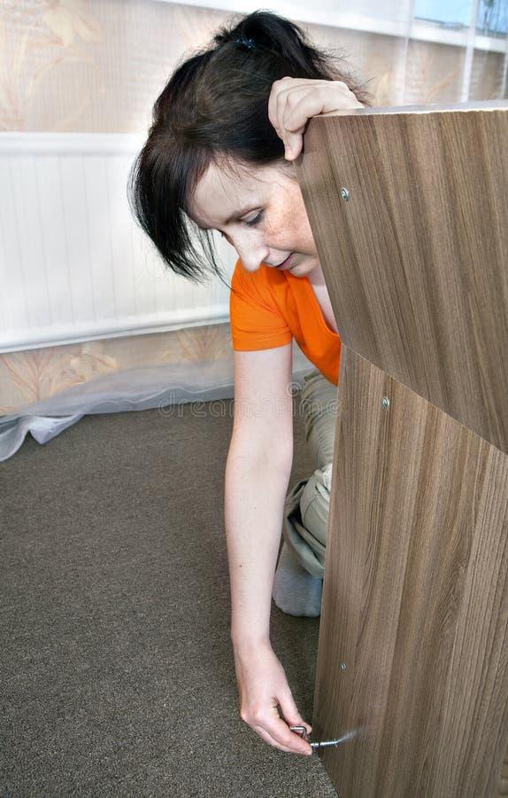 La mano caucásica del ama de casa de la mujer monta los muebles de madera en el hom imagen de archivo