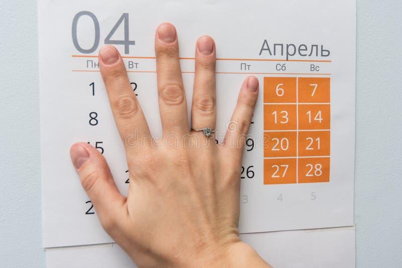 La mano cerró días laborables en una hoja del calendario foto de archivo