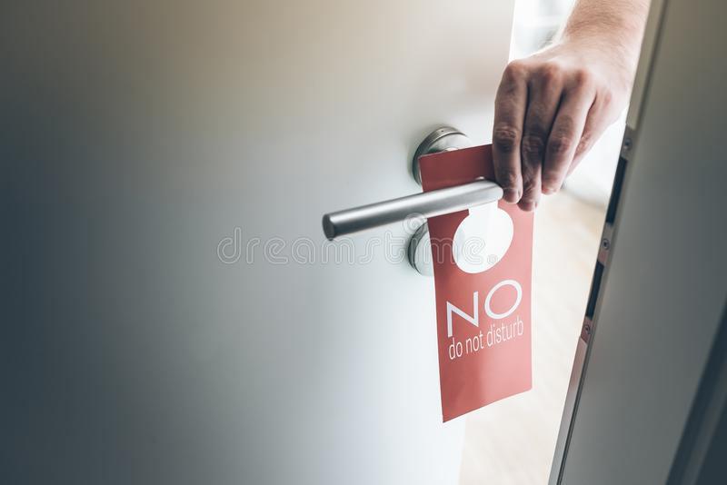 La mano che dispone il rosso non disturba il segno sulla maniglia della porta della camera di albergo fotografie stock libere da diritti