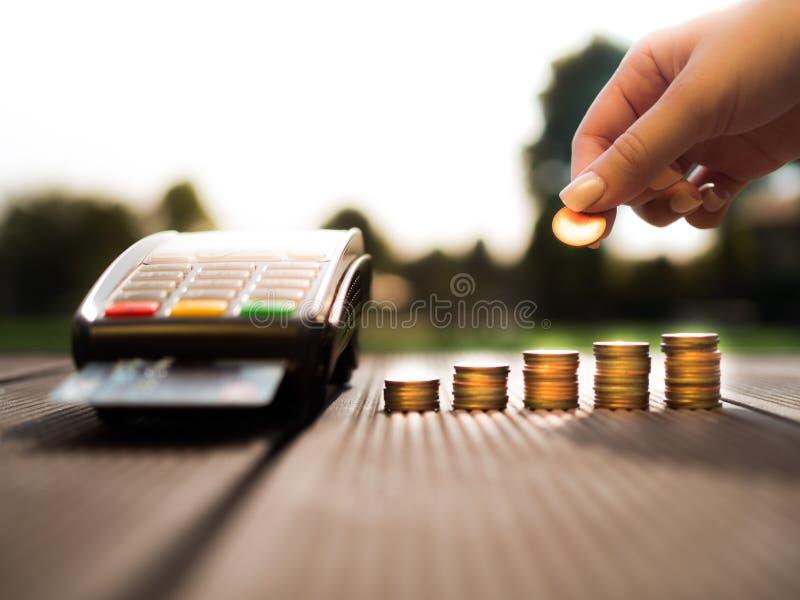 La mano che mette le monete dei soldi impila la crescita ed il colpo delle carte di credito tramite il terminale sul fondo della  fotografie stock
