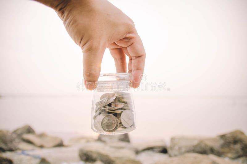 La mano che tiene il barattolo di vetro contiene con la moneta alla spiaggia fotografie stock libere da diritti