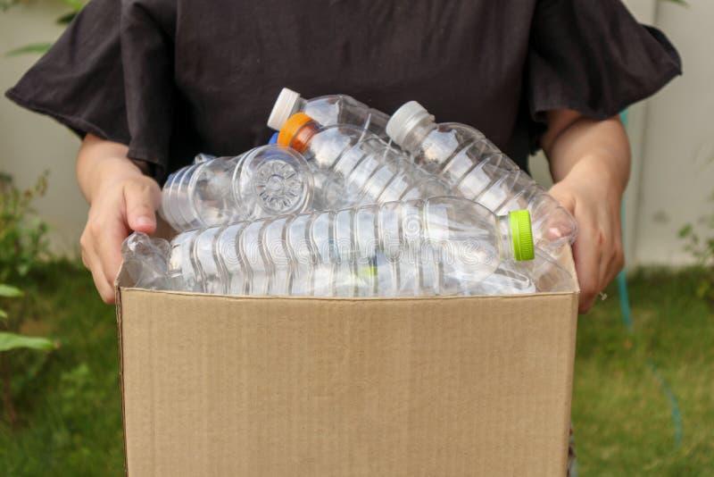 La mano che tiene il marrone ricicla il contenitore di immondizia con le bottiglie di plastica immagine stock