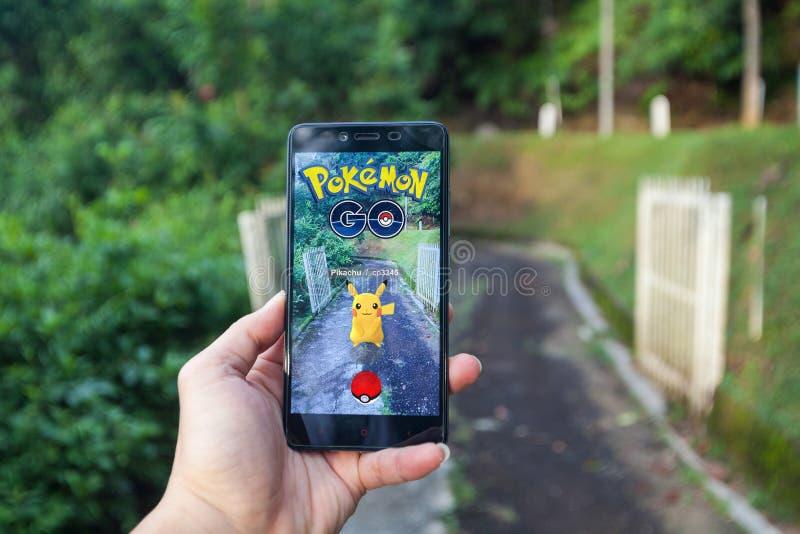 La mano che tiene un cellulare che gioca Pokemon va fotografia stock libera da diritti
