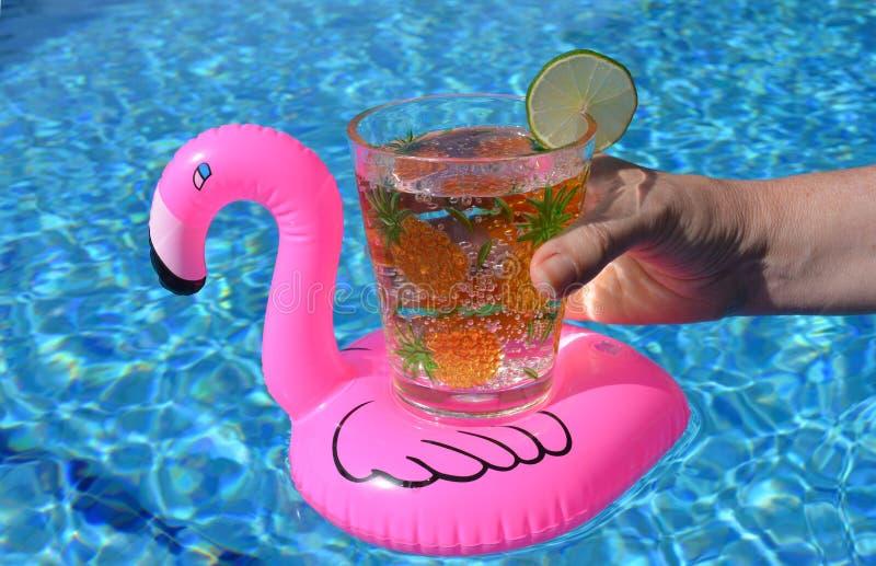 La mano che tiene una bevanda in un fenicottero rosa gonfiabile beve il supporto nella piscina immagine stock libera da diritti