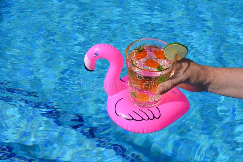La mano che tiene una bevanda in un fenicottero rosa gonfiabile beve il supporto nella piscina immagini stock