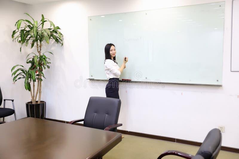 La mano china de la muchacha de la mujer de la señora de la oficina de Asia escribe éxito en el lugar de trabajo del traje del em fotos de archivo