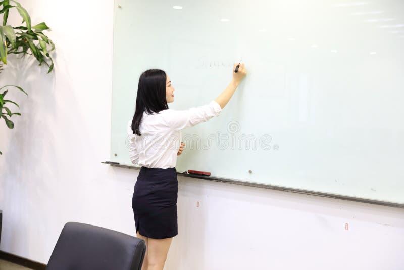 La mano china de la muchacha de la mujer de la señora de la oficina de Asia escribe éxito en el lugar de trabajo del traje del em imagen de archivo libre de regalías