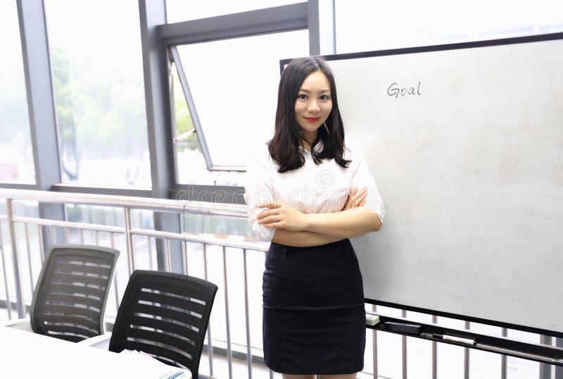La mano china de la muchacha de la mujer de la señora de la oficina de Asia escribe meta en el lugar de trabajo del traje del emp fotografía de archivo