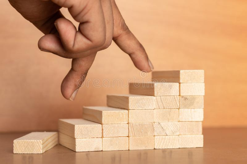 La mano compara a la persona del negocio que salta directamente de parte inferior al top de la escalera de madera del juguete en  imagen de archivo libre de regalías