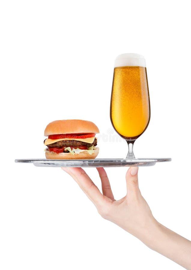 La mano con el guante sostiene la bandeja con la hamburguesa y la cerveza imagen de archivo libre de regalías