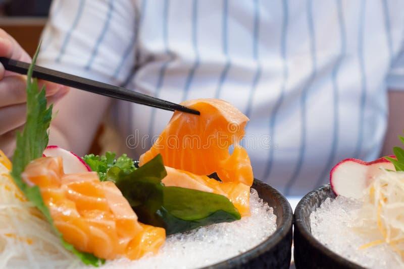 La mano con i bastoncini tiene l'alimento giapponese del sashimi di color salmone fotografia stock