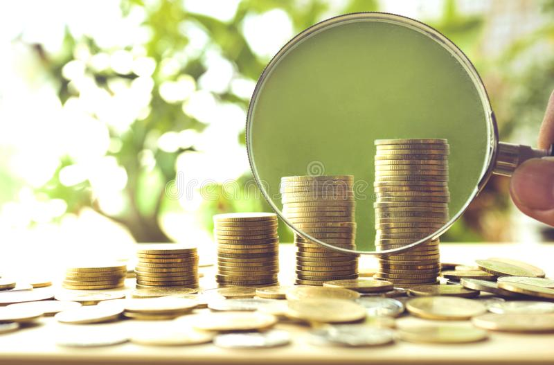 La mano con las monedas de la lupa y del dinero apila el crecimiento fotografía de archivo libre de regalías
