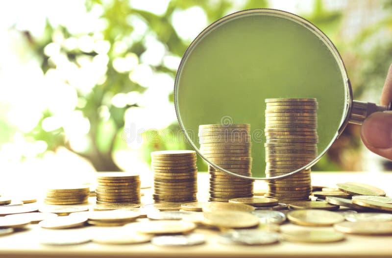 La mano con le monete dei soldi e della lente d'ingrandimento impila la crescita fotografia stock libera da diritti