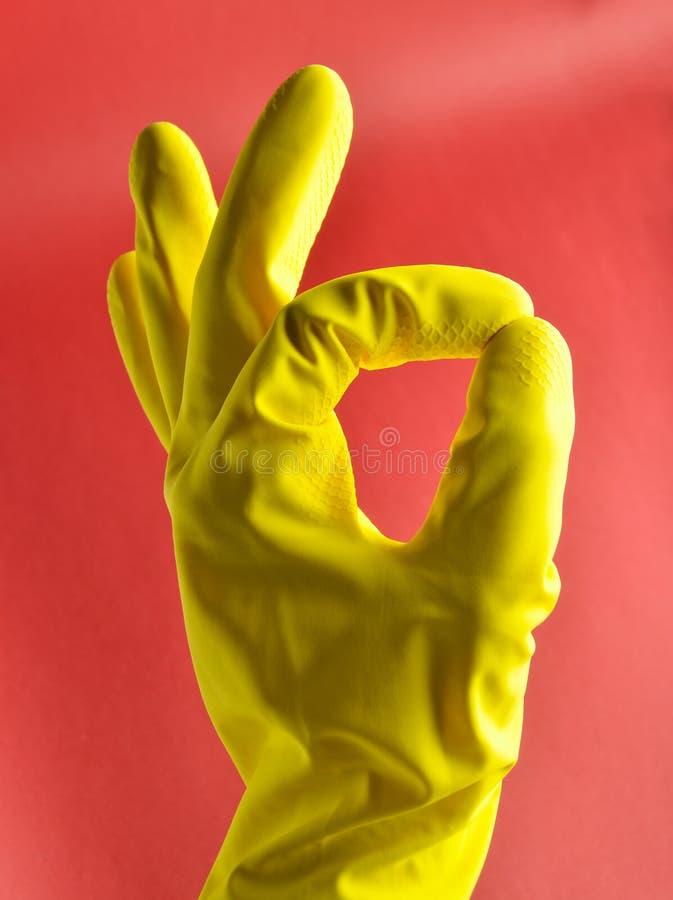 La mano con los guantes de goma amarillos muestra la autorización del símbolo de los pulgares en fondo rojo fotografía de archivo libre de regalías
