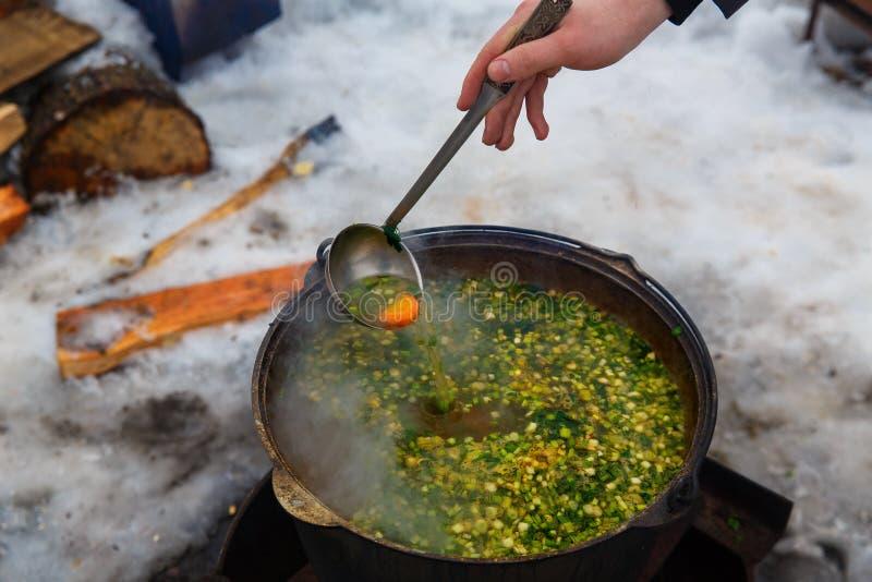 La mano con la minestra del pomeshivat della siviera, che è fatta sul fotografia stock